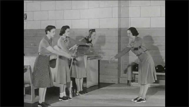 1930s: People sit down in stands. Woman demonstrates bowling technique to girls.