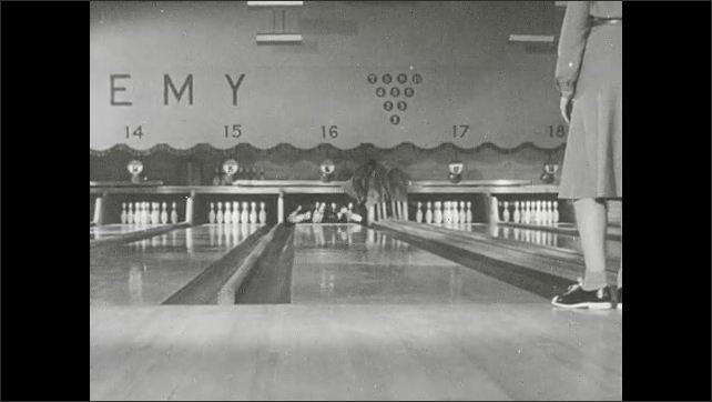 1930s: Woman picks up bowling ball, stands at front of lanes, looks down lane, bowls a strike. Woman holds ball, looks at lane, shuffles forward, falls down.
