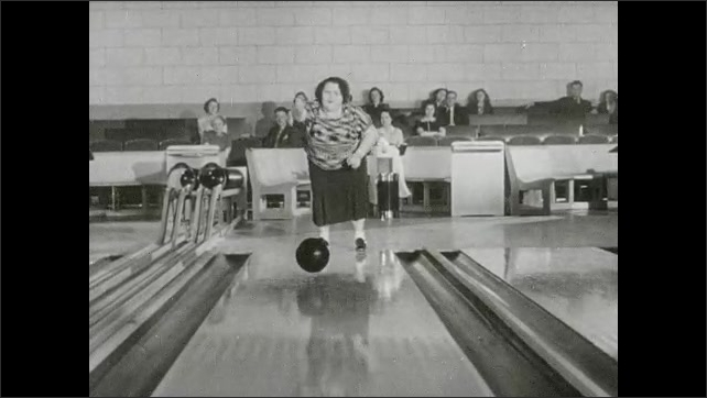 1930s: Woman's feet as she bowls. Woman swings bowling ball. Woman shuffles down lane, stops, gentle bounces ball down lane. Man looks at ball, jumps out of the way, ball knocks down middle pins.