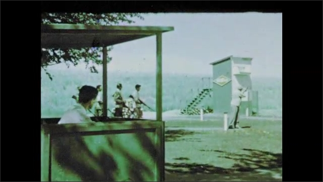 1950s: UNITED STATES: lady and man shoot targets at fairground. Clay pigeon shooting event. Lady shoots gun