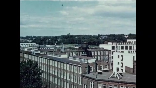 1950s: Winchester repeating arms company. Smokes pours from stacks of factory. Factory and industrial complex panorama.