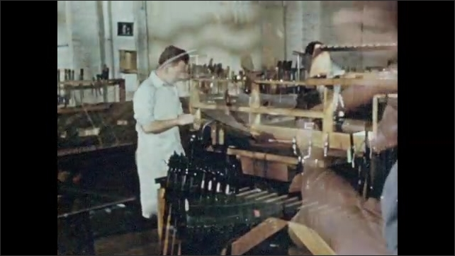 1950s: Hands chisel and carve designs into rifle stocks. Men work at assembly stations. Toolbox of screws and pins.