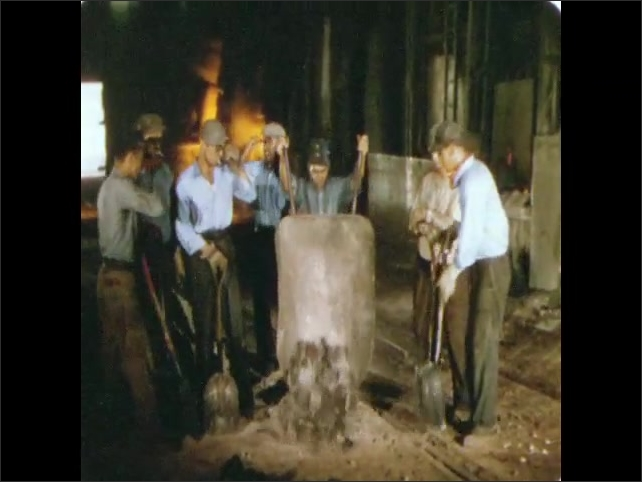 1950s: UNITED STATES: molten metal inside blast furnace. Man takes off blue tinted spectacles. Men shovel manganese into furnace
