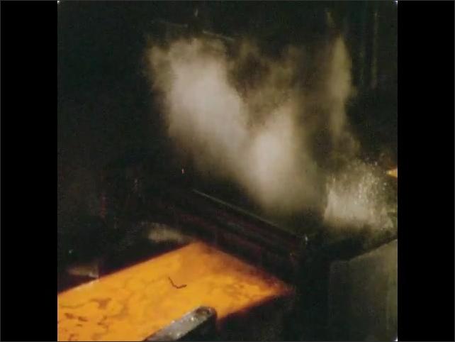 1950s: UNITED STATES: man operates machine behind safety glass. Rolls shape slab of steel.