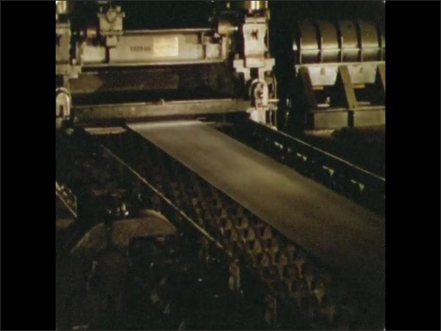 1950s: UNITED STATES: thin sheet of steel on rolling machines. Steel on rollers. Cooling steel sheet