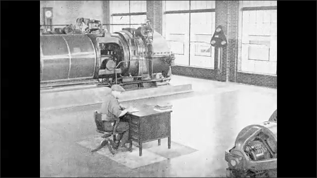 """1930s: Intertitle """"In power house generating room"""". Worker at wooden desk next to heavy machinery."""