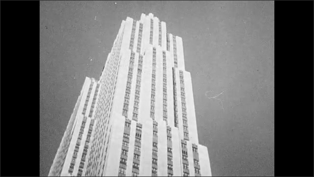 1950s: UNITED STATES: view through trees in mountains. Tall skyscraper building. RCA man in chair.