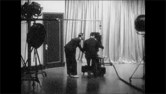 1950s: UNITED STATES: cameraman pushes camera towards actresses. Ladies in front of camera in studio.