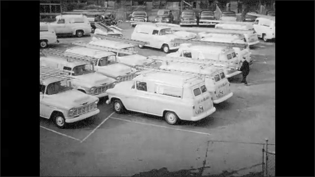 1950s: UNITED STATES: man fits components inside television. Workers box televisions in factory. Vans in car park.