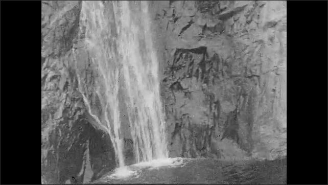 1930s: UNITED STATES: water runs down rocks. View of waterfall. Pool at bottom of waterfall. Men fish in waterfall.