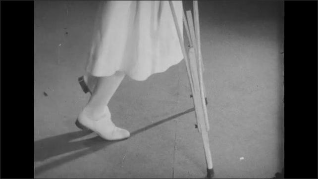 1950s: Woman walks across floor with crutches.