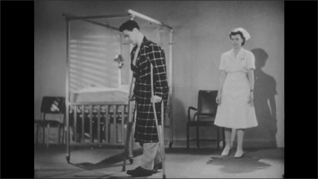 1950s: Man practices walking with crutches, nurse watches.