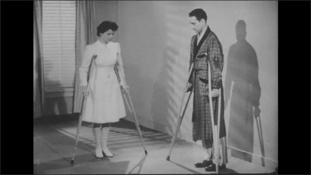 1950s: Nurse leads man through exercises with crutches.