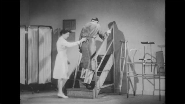 1950s: Nurse helps man walk up stairs using crutch.