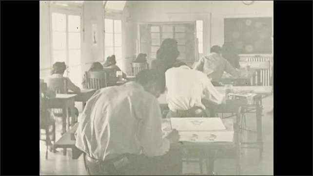"""1930s: Text reads """"Reel IV.  SANTA FE INDIAN SCHOOL IN NEW MEXICO.  TEACHING METHODS IN PAINTING.""""  Classroom.  Teacher walks through room.  Students work on art projects."""