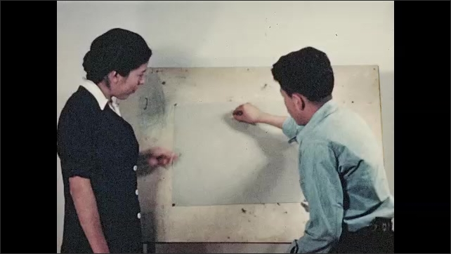1930s: Teacher stands.  Young man sits and attaches paper to board.  Teenage boy draws white circle on paper.