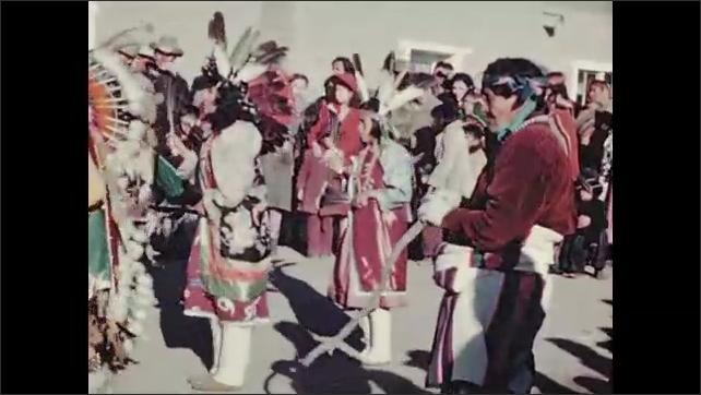 1930s: Men and children at door of adobe home.  Native American ceremonial dance.  People beat drums.