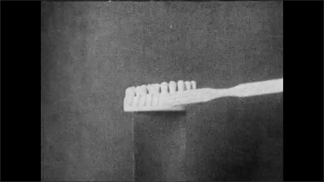 1930s: Text on screen. Hand demonstrates brushing teeth on anatomical model. Nurse demonstrates brushing teeth. Nurse speaks to class.