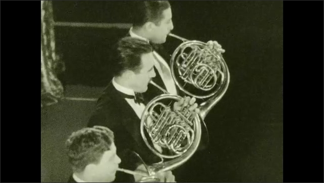 1930s: Four men stand in row placing French horns to mouths. Four men stand playing French horns.
