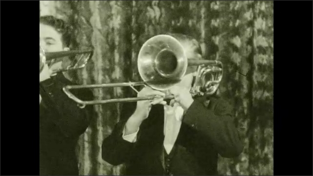 1930s: Four men stand in row playing trombones.
