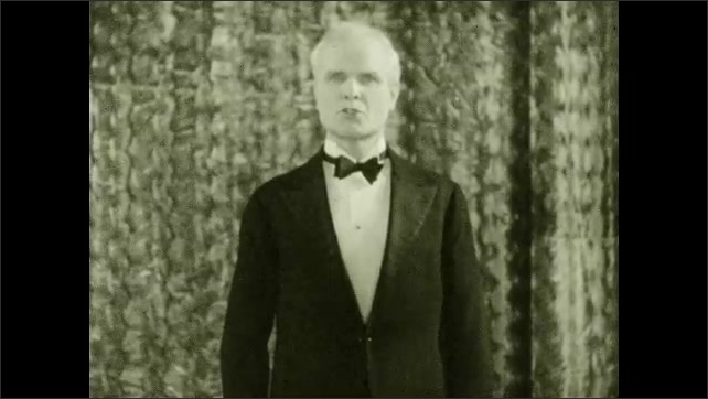 1930s: Man stands in front of curtain talking. Curtain parts and man holding tuba steps forward. Man in front of curtain talking. Man plays tuba.