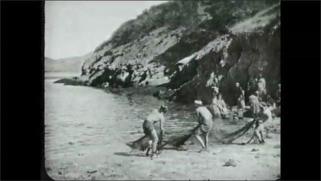 1930s: UNITED STATES: settlement in desert. Fishermen pull nets in from water