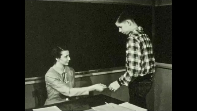 1950s: UNITED STATES: boy gets caught cheating in class test. Boy gives paper to teacher. Boy puts hands in pockets