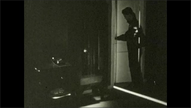 1950s: UNITED STATES: boy sits in dark room by phone. Boy opens room door. Clock on wall. Boy looks in mirror.