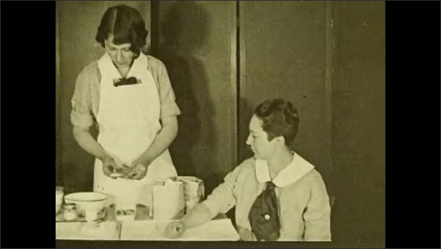 1930s: UNITED STATES: Nurse shows women at meeting how to make bed. Nurse makes bed with sheet. Nurse cleans lady's arm. Patient sits in clinic