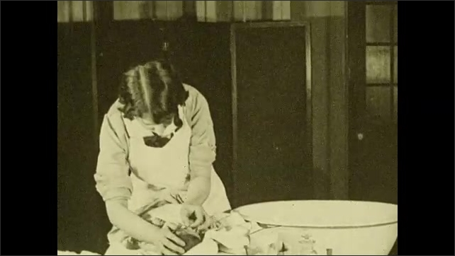 1930s: UNITED STATES: nurse demonstrates how to wash baby. Mothers watch nurse wash baby