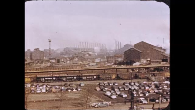 1950s: Pan across factory. Pan across smokestacks, trestles. Metal being formed in factory.