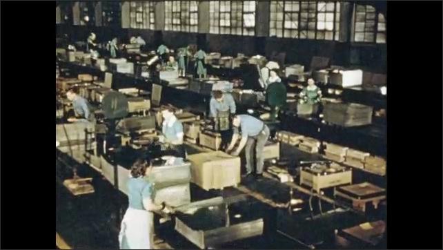 1950s: Pan across equipment, sheet metal in machine. Workers stack metal sheets in factory.