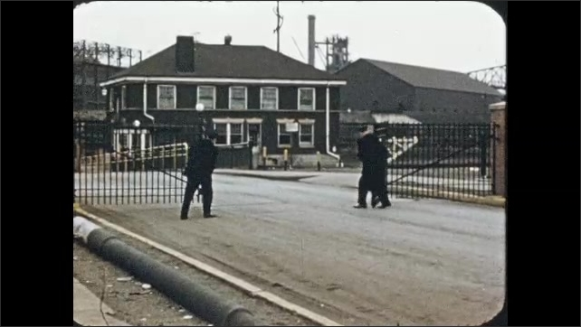1950s: Close up of metal gear. Men close factory gates. Sign on gate.