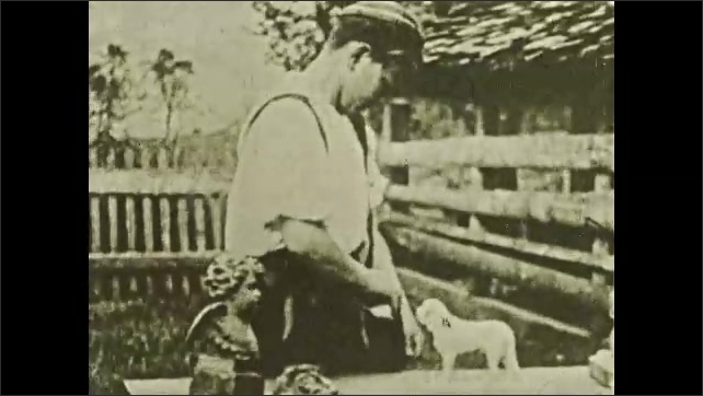 1930s: Boy sets bucket down next to bench then picks up animal carved from wood, looks at it and compares it to one in his shoulder bag. Man stirs pot of food cooking over fire.