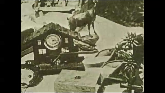 1930s: Woman and boy stand together at table outside. Woman shows boy carved animal. Boy looks at his own carved animal. Boy looks at clock and other items on table. Boy speaks.