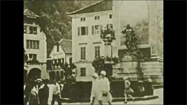 1930s: People walk passed statue and fountain in courtyard. Statue above fountain.