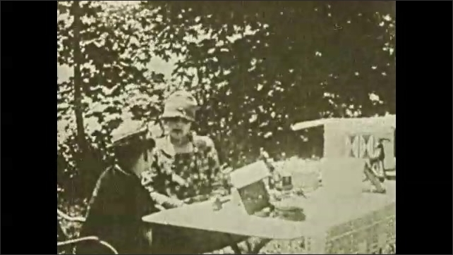 1930s: Water rapidly goes over waterfall. Woman and boy sit at table outside talking then stand up. Title card.