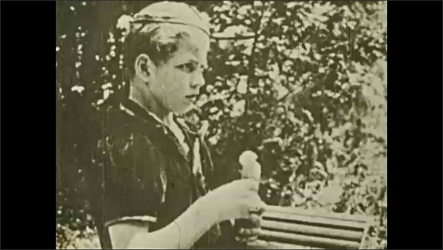 1930s: Boy talking, takes out animal carved from wood from his hip sack and hands it to woman. Title card.