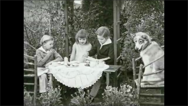 1930s: Close up, boy eating cookie. Kids sitting at table in garden with dog.