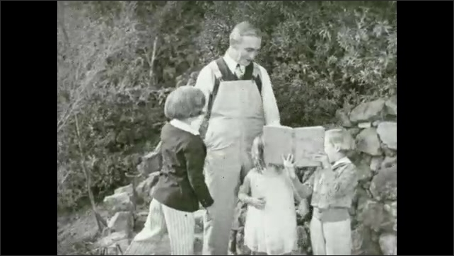 1930s: Cat walking in garden. Man with kids, boy holds up book. Dog playing with cat. Boy shows book to man.
