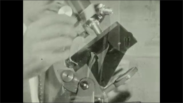 1940s: Man adjusts microscope at table. Close up, man puts slide into microscope.