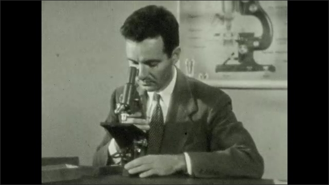 1940s: Man adjusts microscope at table. Close up, moves part on microscope.