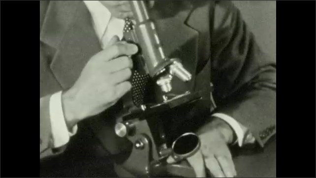 1940s: Man looking into microscope. Magnified image focusing. Man turns knob on microscope. Magnified image focusing.