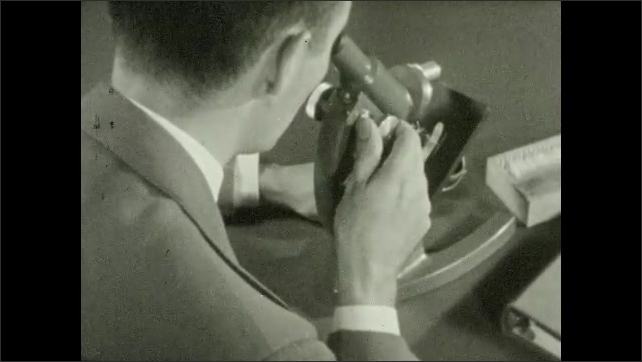 1940s: Close up, man moves part on microscope. Microscope part moving. Man looks into microscope, turns knob. Woman writing, looks into microscope.