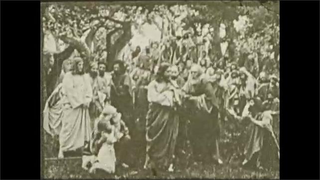 1930s: Crowd is gathered. Jesus gestures and speaks. Man kneels at Jesus' feet.