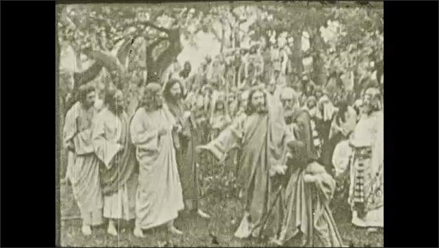 1930s: Crowd is gathered. Jesus gestures and speaks. Man kneels at Jesus' feet. Man stands and walks.