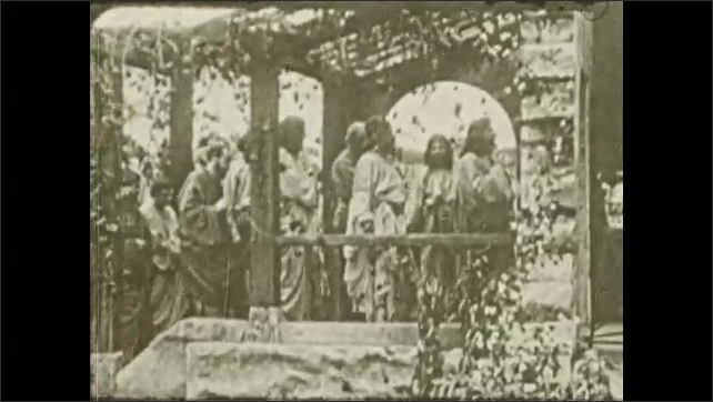 1930s: Jesus and crowd in gazebo. Man talks to Jesus. Group walks into building.