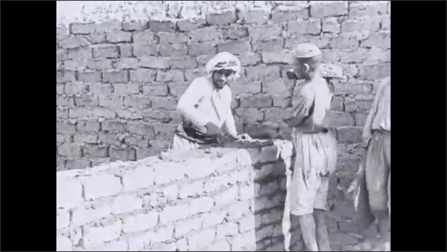 1930s: Man spreads mortar over bricks while man stands holding tray next to him.