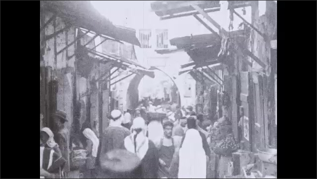 1930s: People and vendors line narrow street between buildings. People walk down street between buildings, lined with vendors.