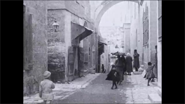 1930s: Narrow road between buildings in Jerusalem. People walk down road.